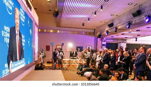 DAVOS, SWITZERLAND - Jan 26, 2018: Journalists watch and listen to the speech of President of the USA Donald Trump on the big screen in lobby of World Economic Forum Annual Meeting 2018 in Davos