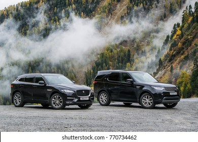 DAVOS, SWITZERLAND - OCTOBER 3, 2017: Jaguar F-Pace and Land Rover Discovery 5 made a long way to a mountain pass Umbrail in Switzerland. Photo taken on the serpentine road in the Alps near Davos.