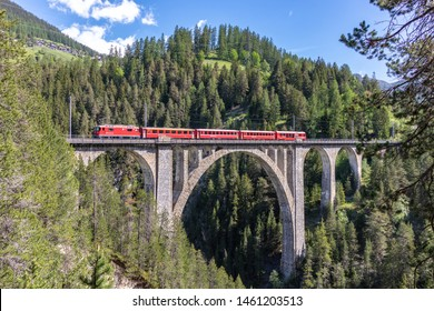 Davos-Wiesen, Switzerland-June 07,2019 View from the historic Wiesener Viaduct with a train of the Rhaetian Railway near the town Davos Wiesen, Swiss Alps