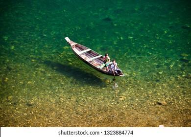 DAWKI, MEGHALAYA, INDIA - 03 FEBRUARY 2019: A local boatman ferries a single passenger across the crystal clear turquoise waters of the Umngot river near the Indo-Bangladesh border.