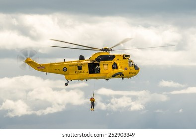 DAWLISH, UNITED KINGDOM - AUGUST 23, 2014: Royal Navy Sea King Search and Rescue Helicopter Flying at the Dawlish Airshow Demonstrating Winch Rescue