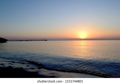 Dawn above the sea. Beach, waves, sea, pier on the background of the rising sun.