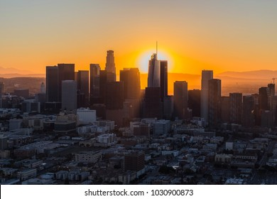Dawn aerial view of rising sun behind downtown Los Angeles in Southern California.