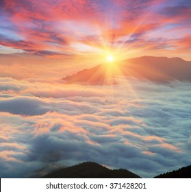 At dawn, after a warm rain ridges Chornogory haze enveloped with rays of sunshine. Sea fog in the pink light is very beautiful and fabulous, picturesque vague wave rolled on the slopes of the peaks