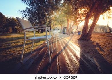 Dawn among palm trees and chairs along the paths and watering the lawn near the beach, camping, Greece