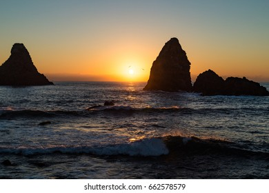Dawn in the bay of Acitrezza, Sicily, with a silhouette view of its typical lava stacks (Faraglioni).