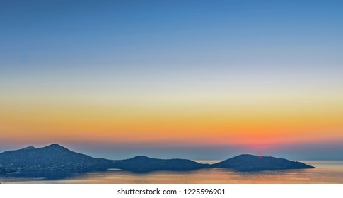 Dawn the bay at Elounda.  The sun comes up behind a headland and the dawn sky is reflected in the water.