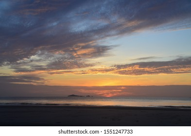 Dawn beauty, picturesque tropical orange coloured stratocumulus cloud coastal sunrise seascape in a blue sky over the ocean with sea water reflections. Nature background image. Huay Yang, Thailand.