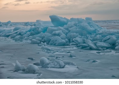 dawn in the blue hummocks of ice lake baikal, in a snowy field in winter on a journey.