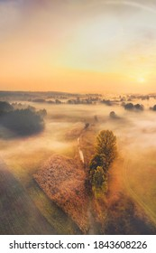 Dawn calm village landscape - autumn trees over the river in clouds of fog - aerial shoot at dawn with an atmospheric perspective