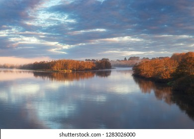 Dawn in a fog on the river. Autumn morning. A fog over water. The sun in a fog.  Early morning sunrise glow and rising mist over the Waikato river in North island