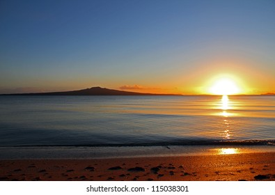 The dawn of a new day as the sun rises beside Rangitoto Island, Auckland, New Zealand