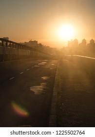 Dawn on the road towards the Sun. Dazzling morning sun