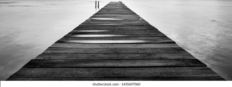Dawn on a wooden jetty stretching into the silent ocean in stunning black and white
