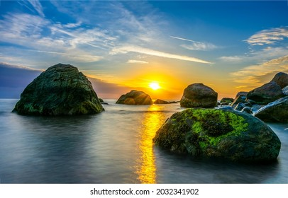 Dawn over the bay among the mountains. Sea boulders at dawn. Beautiful sunrise over sea boulders. Boulder beach at dawn