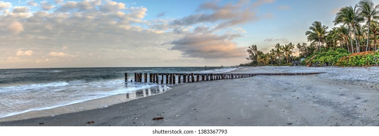 Dawn over a dilapidated pier on the beach in Port Royal in Naples, Florida.
