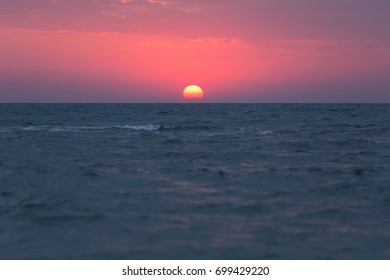 Dawn over the sea, the red sun rises above the horizon, waves on the water
