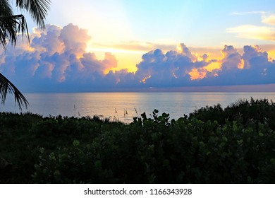 Dawn over Singer Island, Florida, with colorful hues in the clouds reflecting on the ocean.