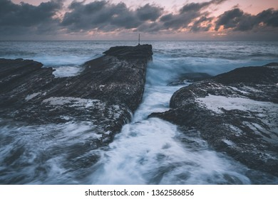 Dawn skies with a pre sunrise glow behind heavy grey clouds. Moody seas surge forth waves that batter the rocks and crash haphazardly upon the rocky shore