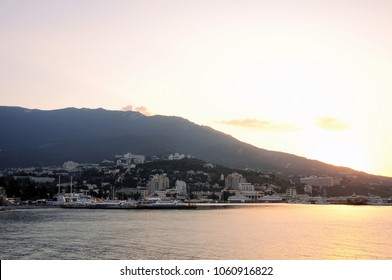 Dawn of the sun on the sea, in the port of the city of Yalta, with a view of the houses and mountains. Crimea, Ukraine, background
