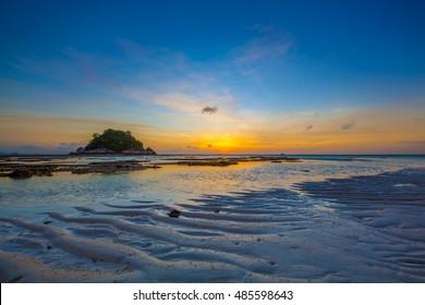 Dawn sunrise at Ko Lipe Island eastern beach overlooking Uma Sen Island rising low tides with wavy sand and mud