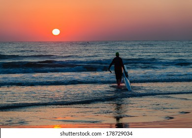 Dawn Surf-Ski Paddler Beach Ocean  Surf-ski paddler silhouetted beach entry into ocean waters for training at dawn sun rising in horizon sky