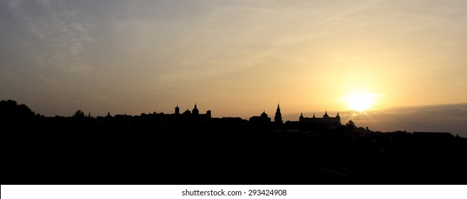 Dawn in Toledo, Castilla La Mancha,Spain, backlit, yellow background and black silhouette sky over the city silhouette view of the main medieval monuments,creative