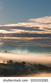 Dawn veiled by clouds and fog on the hills. Dark mountains create a romantic and mysterious atmosphere