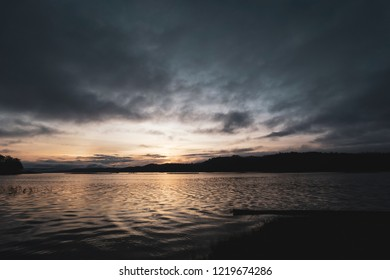 Dawning landscape by a lakeside with beautiful light from the sunrise and dramatic sky