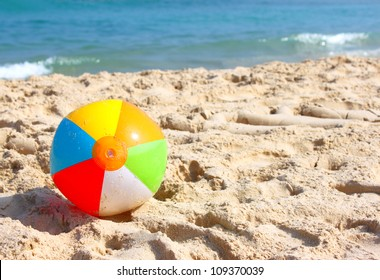 Day at the beach with a beach ball in the foreground.