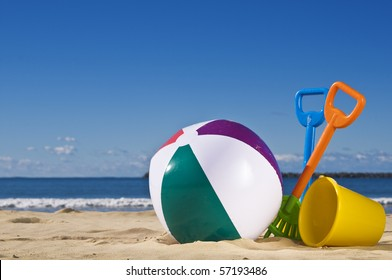 Day at the beach with a beach ball, spade and bucket in the foreground.