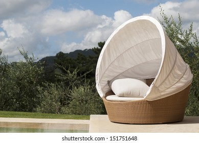 A day bed by a pool with olive trees in the background