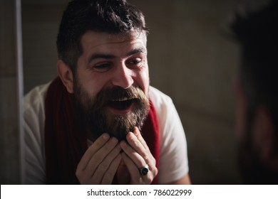 The day begins with taking care of the face. Portrait of a bearded man with red towel, washes face and looking at his reflection in the mirror in bathroom. Over the years, the skin becomes wrinkled.
