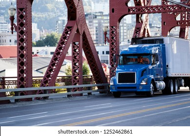 Day cab for local freights and delivery blue big rig semi truck transporting commercial cargo in refrigerated semi trailer moving on Broadway Bridge across Willamette river in down town Portland