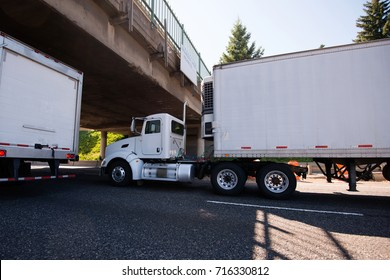 Day cab white big rig semi truck with reefer trailer and refrigeration unit on it to maintain a certain temperature of the cargo during transport going under the bridge on roadside with traffic