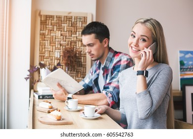 Day in cafe. Young couple in cafe with stylish interior. Students having delicious coffee drinks. Woman using mobile phone and man reading book. Woman looking at camera