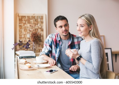 Day in cafe. Young couple in cafe with stylish interior. Students having delicious coffee drinks. They chatting while drinking coffee