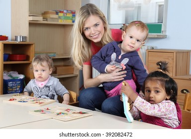 A Day care or kindergarten kids and teacher playing with a puzzle