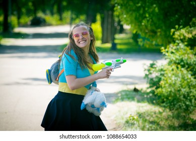 The day of children in high school. Girls and boys shoot water from a toy gun. Entertainment for graduates