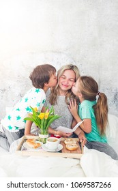Mother´s Day - children surprise their mother with breakfast in modern bed