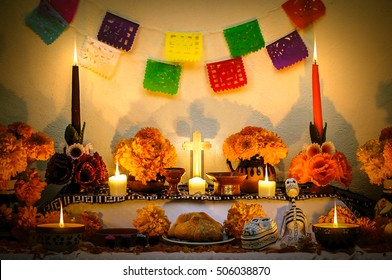 Day of the Dead altar with cempasuchil flowers and candles.