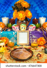 Day of the dead altar with sugar skulls and candles, blue background
