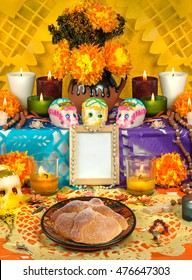 Day of the dead altar with sugar skulls and candles, yellow background
