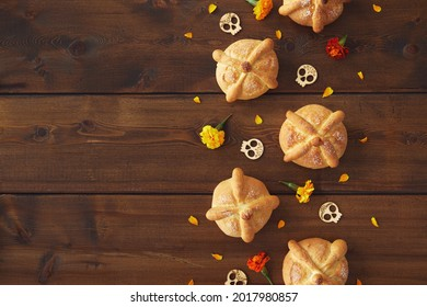 Day of the dead, Dia De Los Muertos celebration party Background With bread of death or Pan de Muerto, Skulls, marigolds flowers on dark wood table with Copy Space. Traditional Mexican culture