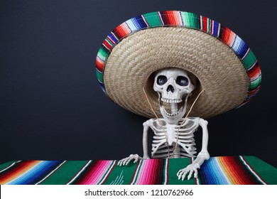 Day of the Dead. Human skeleton wearing a beautiful serape sombrero (hat) and sitting at a table covered with a colorful serape blanket