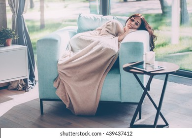 Day dreaming beauty. Beautiful young woman sleeping in a big comfortable chair at home while being covered with blanket