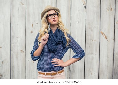 Day dreaming trendy blonde holding pencil on wooden background