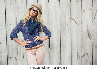 Day dreaming trendy blonde posing on wooden background