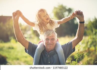 Day full of fun and smile. Grandfather and granddaughter spending time together in nature. Copy space.