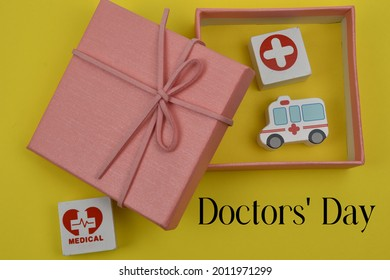 Doctor's Day with a gift box containing a health icon and an ambulance vehicle with a yellow background
